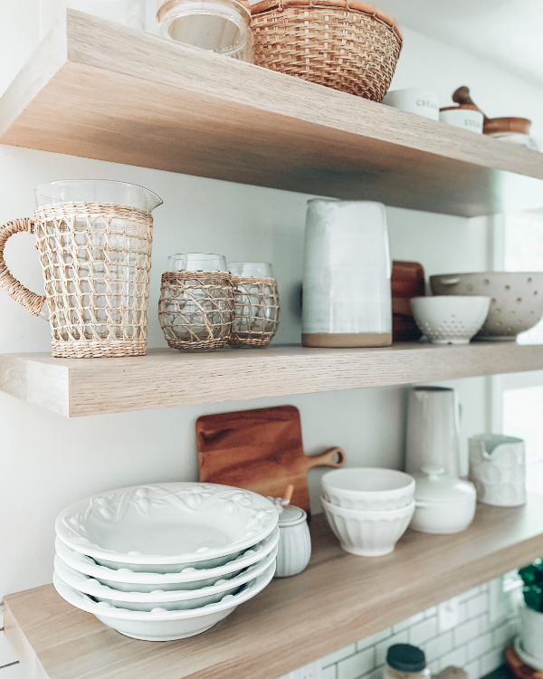 The floating shelves styled with neutral kitchen decor